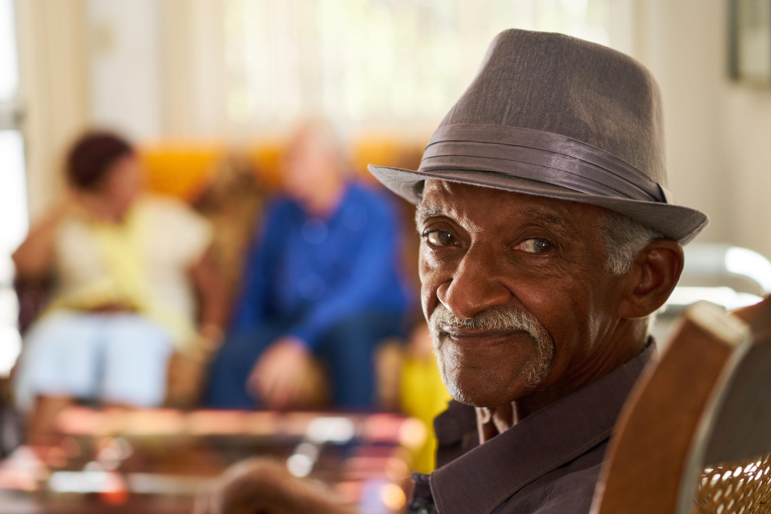 Senior Black Man With Hat Looking At Camera In Nursing Home